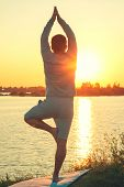 A Young Man Is Standing On The Lake At Sunset, Doing Yoga. Stands In A Pose Of Tree A Sathi Yoga. Ba poster