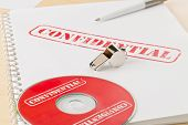 Chrome Whistle On Documents And Cd Or Dvd With Confidential Top Secret Information On Wooden Office  poster