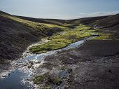 Small Stream From Melting Ice With Lush Vivid Green Wet Moss In Black Lava Hills In Landmannalaugar  poster