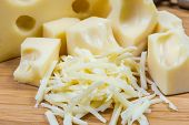 Grated Swiss-type Cheese Against Of Slices Of The Same Cheese On A Bamboo Wooden Cutting Board Close poster