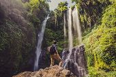 Man In Turquoise Dress At The Sekumpul Waterfalls In Jungles On Bali Island, Indonesia. Bali Travel  poster