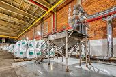 Large Industrial Warehouse Of Chemicals. Large White Bags Filled With Powder Are Arranged In Long Ro poster