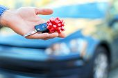 Closeup Male Hand Of New Black Car Is Holding Gift, Surprise, Keys With Red Bow. Lucky Driver Is Goi poster