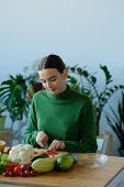 A Vegan Girl In A Green Sweater Cuts With A Knife Fresh Tomatos. Fresh Healthy Vegan And Vegetarian  poster