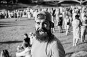 Hipster In Cap Happy Celebrate Event Fest Or Festival. Man Bearded Hipster In Front Of Crowd. Open A poster