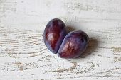 Ugly Plum. Spoiled Plum In The Shape Of A Heart On A White Wooden Background. Ugly Fruit. Funny Food poster