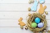 Homemade Bunny Cookies, Pastel-colored Easter Eggs In A Nest And Quail Eggs On The Light Wooden Back poster