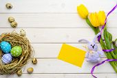 Easter Eggs In A Nest, Quail Eggs, Tulips, A Ribbon, A Knitted Bunny And A Yellow Card On The Wooden poster
