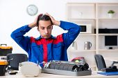 Young repairman repairing air-conditioner at warranty center poster