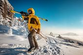 Skier With Ski In Hands Goes Uphill For Backcountry Skiing. Ski Resort Concept poster