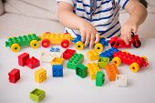 Toddler Child Playing Multi-colored Cubes On The Table. Colorful Plastic Bricks For The Early Develo poster