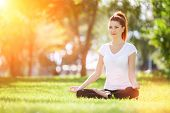Yoga outdoor. Happy woman doing yoga exercises, meditate in sunny park. Yoga meditation in nature. C poster