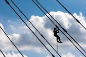 Silhouette of construction climber against blue sky