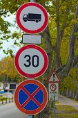 Three Road Signs On Post Against Old Trees. No Goods Vehicles Warning Sign, Speed Limit Sign And No  poster