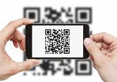 stock photo of barcode  - Male hands holding smart phone with qr code on it - JPG