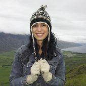 Hispanic woman wearing hat and gloves