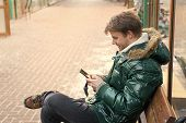 Man Unshaven Wear Warm Jacket And Hold Smartphone Snowy Urban Background. Guy Sit Bench Interact Sma poster