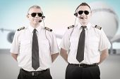 Cheerful airline pilots wearing uniforms with epauletes and headsets standing with airliner in background.
