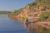 canoe paddler (senior male) on a mountain lake - Horsetooth Reservoir near Fort Collins, Colorado at