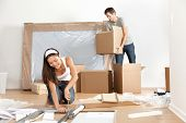 Couple moving in new home house. Young interracial couple in moving in mess. Asian woman, Caucasian