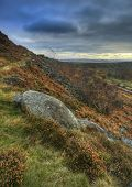 Abandoned Millstones On Curbar Edge In Peak District National Park With Froggatt's Edge In Backgroun