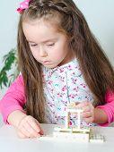 Niña jugando Domino en la mesa