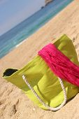 Green Beach Bag On The Seacoast And Pink Shawl