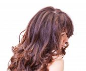 pic of auburn  - Over the shoulder side view studio portrait of a pensive young woman with beautiful long wavy auburn hair - JPG