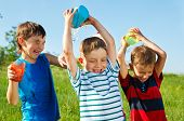 Happy boys with plastic containers splashing water over one another's heads