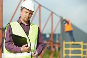 picture of labourer  - site manager builder worker in uniform and safety protective equipment at construction site in front of metal construction frames - JPG