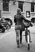 Woman Walking Bike On The Sidewalk