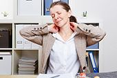 Senior business woman with pain massaging her neck in her office