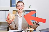 Happy senior business woman pointing red arrow to piggy bank in her office