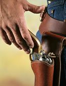 stock photo of gunfighter  - cowboys hand at waist level reaching for gun as if to draw - JPG