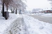 stock photo of freezing temperatures  - Slush and snow in the sidewalk in a cold winter day - JPG