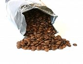 Whole coffee beans scattered on white background with silver packaging