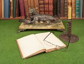 Antique leather books lamp and reading glasses on green blotter