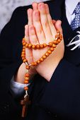 stock photo of rosary  - Hands of the boy going to the First Holy Communion set in amen with a rosary - JPG