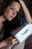 stock photo of obituary  - Close up portrait of young widow holding obituary - JPG