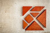 seven tangram wooden pieces, a traditional Chinese puzzle game, rough white painted barn wood backgr
