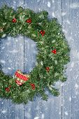 Christmas wreath hanging from rustic door with falling winter snow