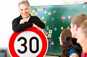 Driving school - driving instructor and student drivers look at a tempo thirty Road sign, in the bac