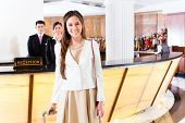 stock photo of trolley  - Asian Chinese woman arriving at front desk of luxury hotel in business clothes with trolley - JPG