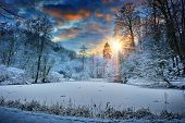 stock photo of cold-weather  - Spectacular orange sunset over winter forest lake - JPG