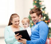 christmas, x-mas, winter, family, people, happiness, modern technology concept - happy parents and a