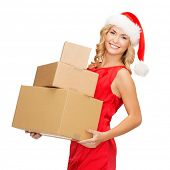 christmas, x-mas, winter, happiness concept - smiling blonde woman in santa helper hat with many par