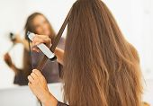 Woman Straightening Hair With Straightener . Rear View