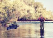 stock photo of fly rod  -  a person fly fishing in a river with a fly in the foreground vintage toned  - JPG