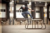 Skateboarder Doing A Crooked Grind  On A Picnic Table