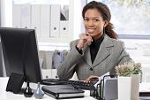 Portrait of happy afro businesswoman sitting at desk, working with computer, smiling, hand on chin.